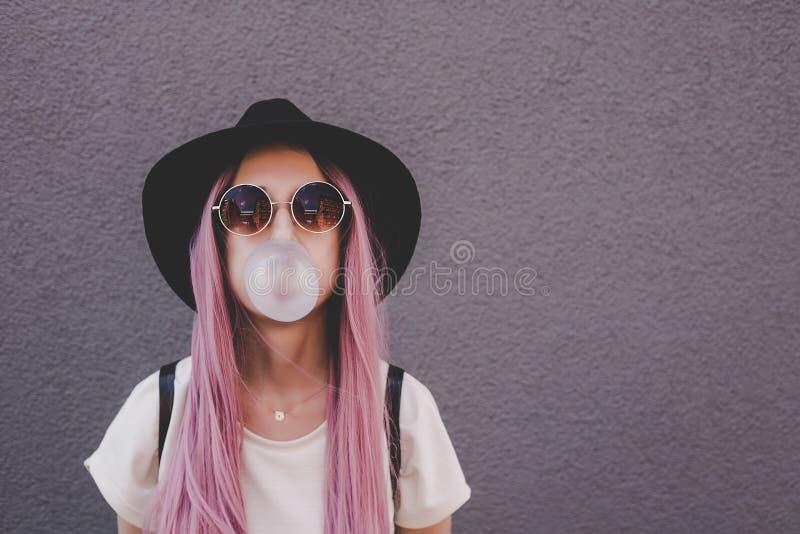 Giovane donna dei pantaloni a vita bassa con capelli rosa lunghi che soffiano una bolla con di gomma da masticare fotografia stock
