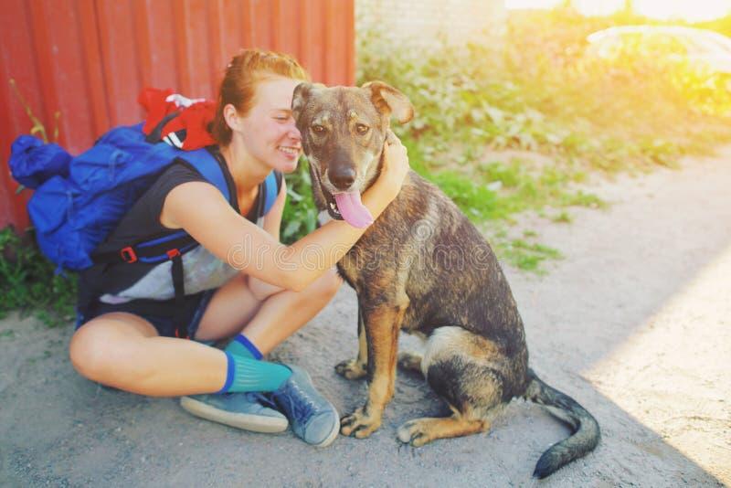Giovane donna dei pantaloni a vita bassa del ritratto con lo zaino che bacia l'animale domestico felice di aria aperta del cane e immagini stock libere da diritti