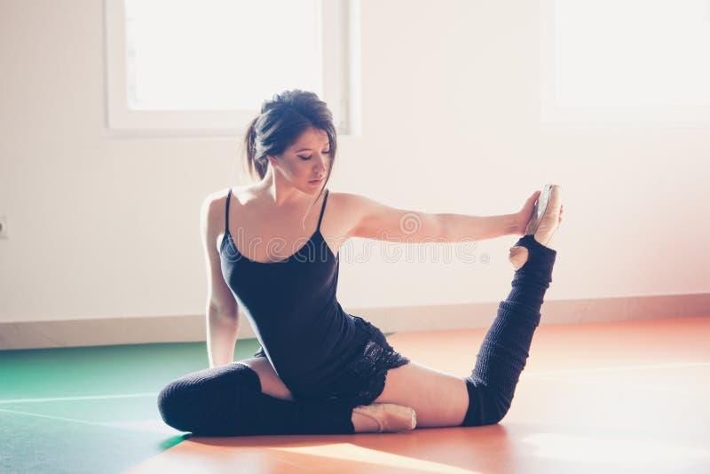 Giovane donna del ballerino di balletto che fa allungamento immagini stock