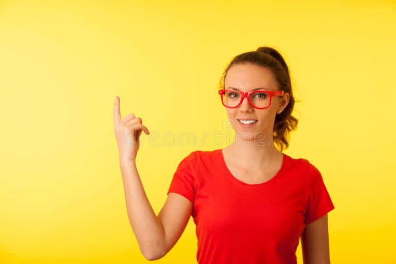 Giovane donna del geek nel punto rosso della maglietta nello spazio della copia sopra vibrante fotografie stock