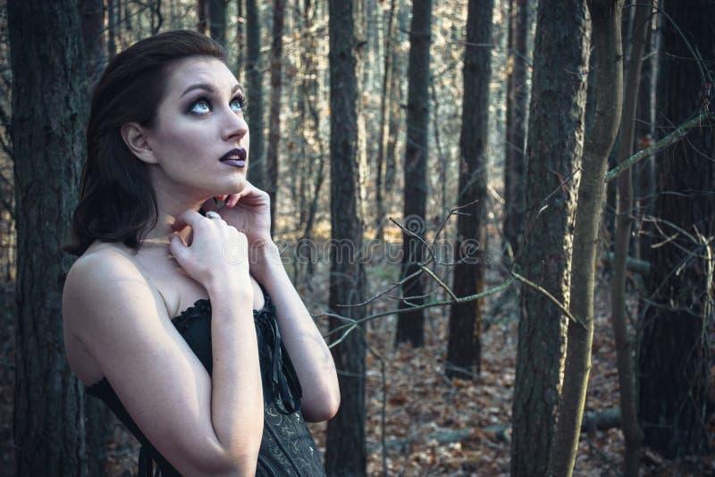 Giovane donna del goth in una foresta di autunno fotografia stock libera da diritti