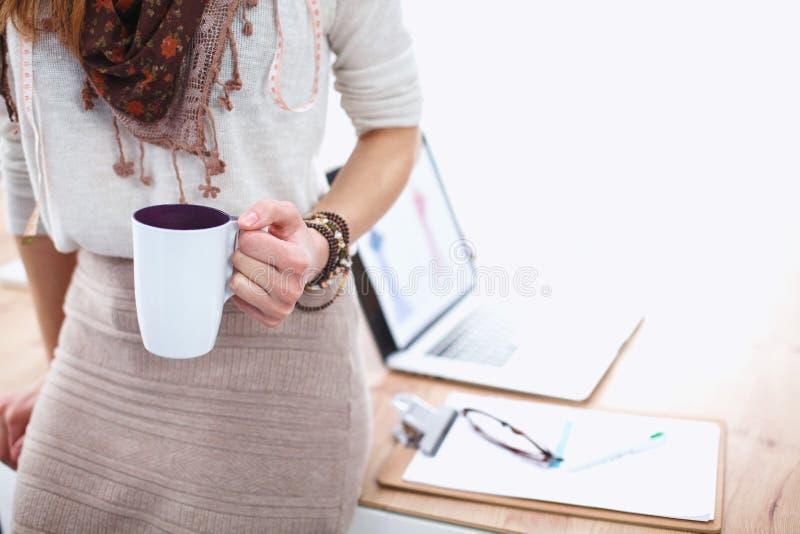 Giovane donna del primo piano che tiene tazza di caffè immagine stock