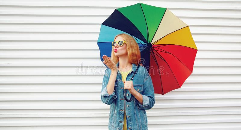 Giovane donna del ritratto che tiene ombrello variopinto che soffia le labbra rosse che inviano bacio dolce dell'aria sul fondo b fotografia stock