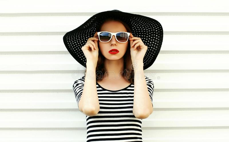 Giovane donna del ritratto di modo in cappello di paglia nero di estate che posa sulla parete bianca immagini stock libere da diritti