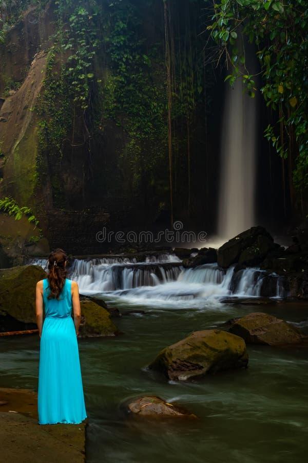 Giovane donna del viaggiatore alla cascata in foresta tropicale, Ubud, Bali Cascata di Sumampan Vista dalla parte posteriore Temp fotografia stock