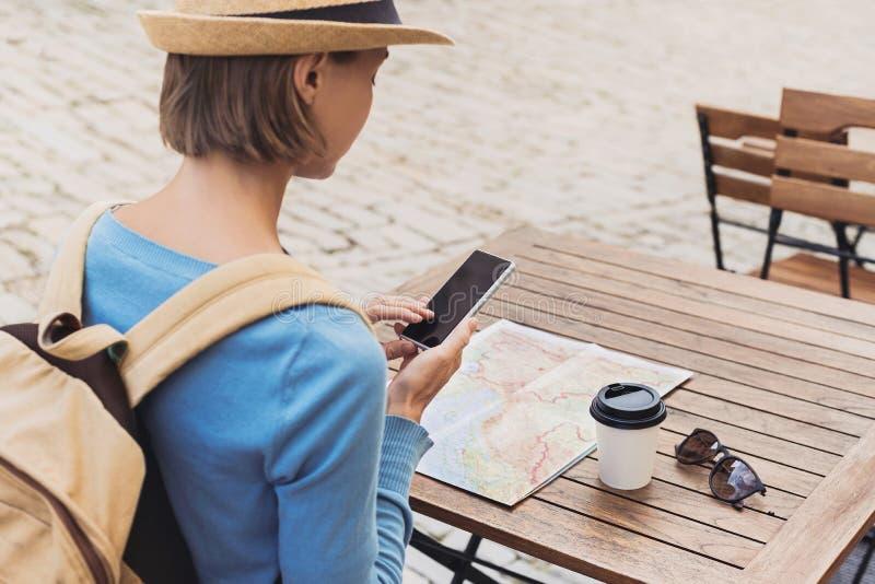 Giovane donna del viaggiatore che si siede in un terrazzo del caffè ed in un viaggio di progettazione con la mappa e lo smartphon fotografia stock