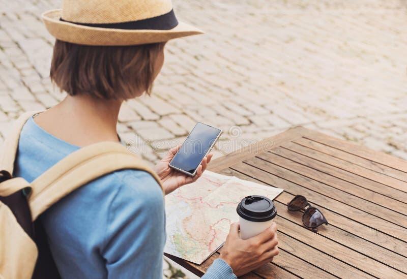 Giovane donna del viaggiatore che si siede in un terrazzo del caff? ed in un viaggio di progettazione con la mappa e lo smartphon immagine stock