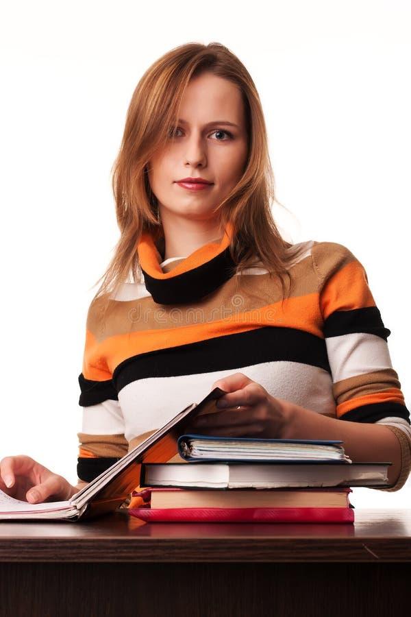 Giovane donna dell'insegnante che si siede allo scrittorio immagini stock libere da diritti