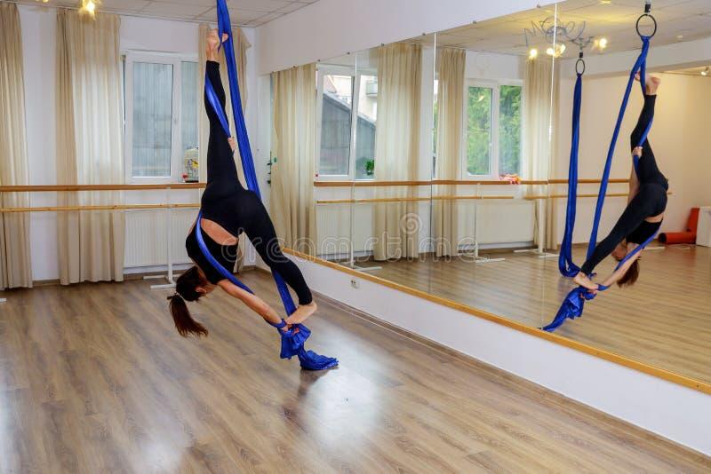 Giovane donna della ginnasta che fa ginnastica sulla corda nella palestra aerea di forma fisica fotografia stock libera da diritti