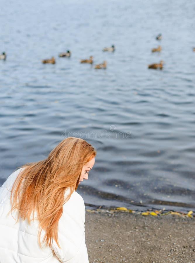 Giovane donna della testarossa che cammina nel parco di autunno vicino all'acqua fotografia stock