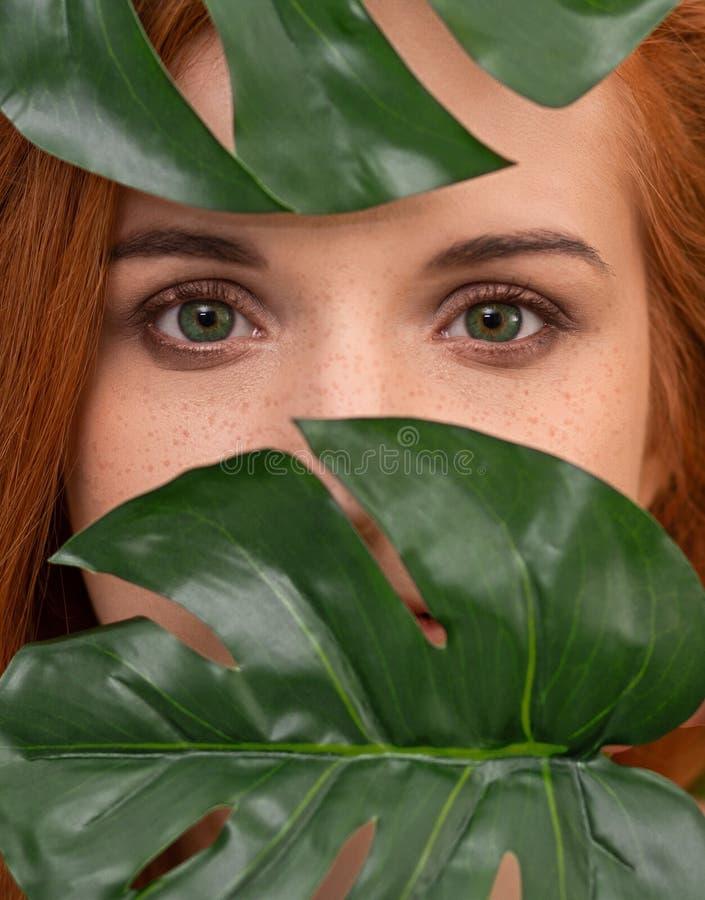 Giovane donna della testarossa con trucco naturale alle foglie verdi di monstera fotografia stock