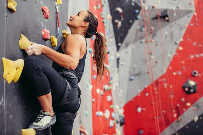 Giovane donna dello scalatore che scala sulla roccia pratica nel centro rampicante, bouldering fotografie stock