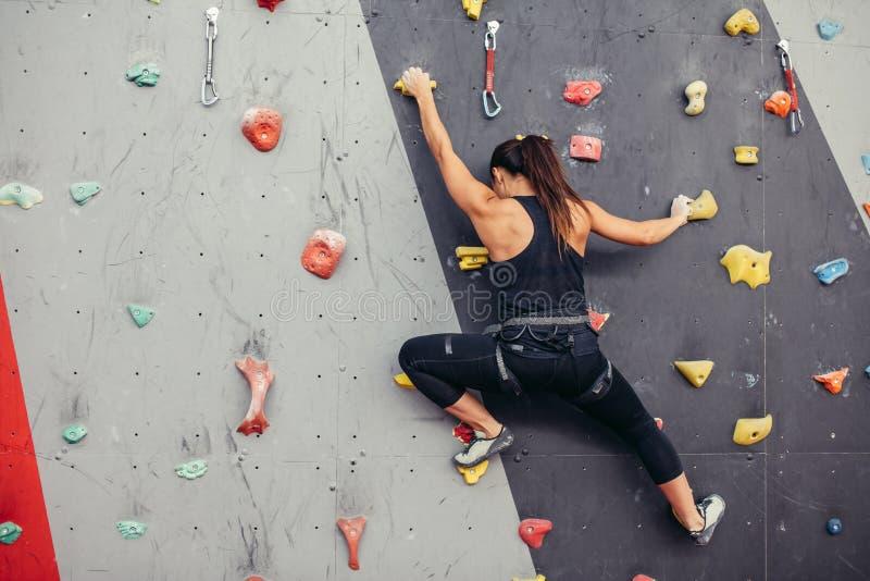 Giovane donna dello scalatore che scala sulla roccia pratica nel centro rampicante, bouldering immagini stock libere da diritti