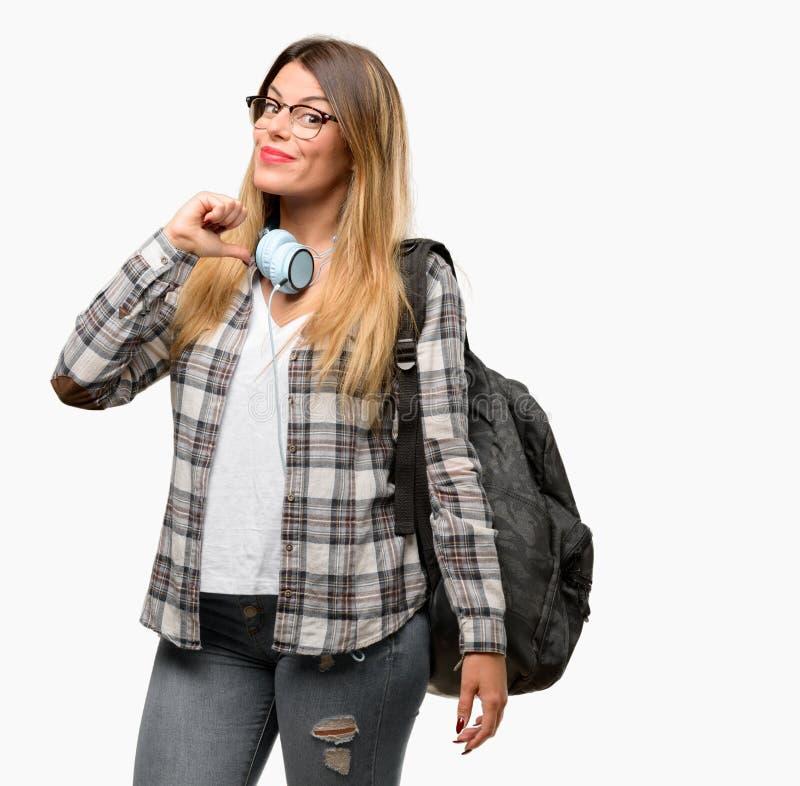 Giovane donna dello studente con le cuffie e lo zaino fotografia stock libera da diritti
