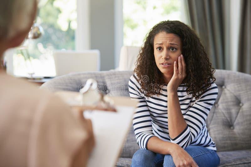 Giovane donna depressa che ha terapia con uno psicologo fotografia stock