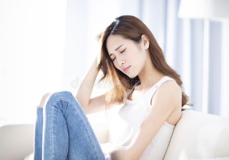 Giovane donna depressa che si siede sul sofà immagini stock