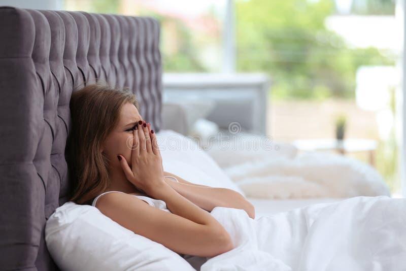 Giovane donna depressa a letto a casa fotografia stock libera da diritti