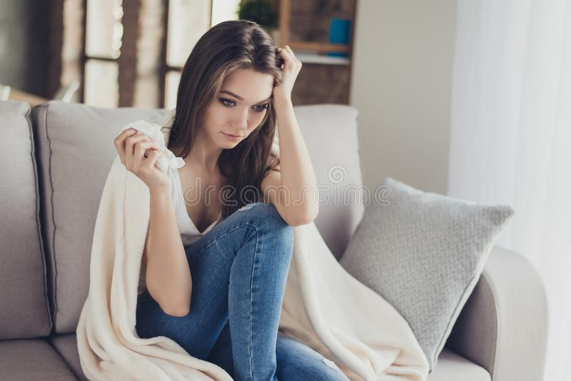 Giovane donna depressa preoccupata che se lo siede sul sofà con la coperta sopra fotografia stock libera da diritti