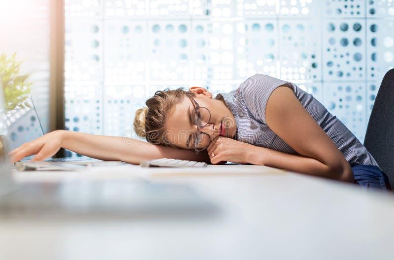 Giovane donna di affari addormentata al suo scrittorio in un ufficio fotografie stock libere da diritti