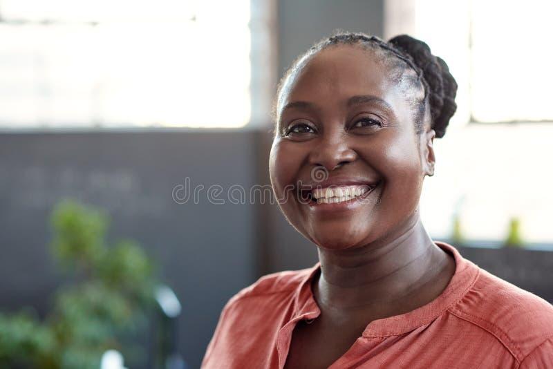 Giovane donna di affari africana che sorride con confidenza in un ufficio immagini stock libere da diritti