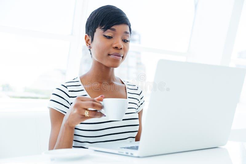 Giovane donna di affari afroamericana pensierosa che si siede nel luogo di lavoro immagine stock libera da diritti