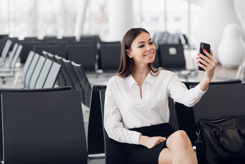 Giovane donna di affari all'aeroporto internazionale, facente selfie con il telefono cellulare ed aspettante il suo volo femmina immagini stock libere da diritti