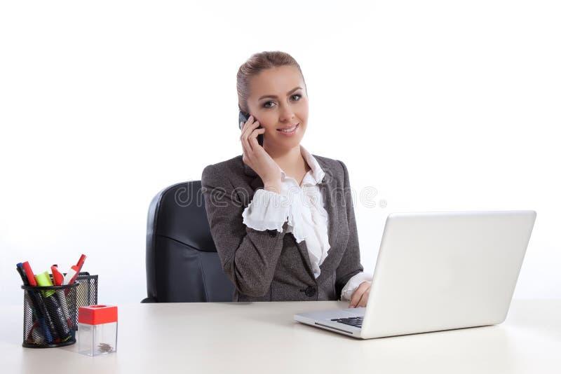 Giovane donna di affari all'ufficio che chiama dal telephon fotografie stock