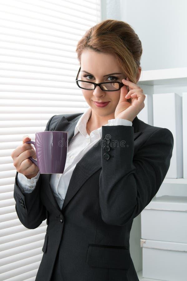 Giovane donna di affari allegra che decolla i suoi vetri immagini stock