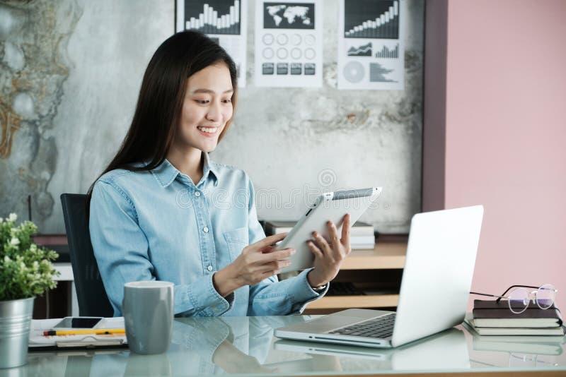 Giovane donna di affari asiatica che per mezzo della compressa con il fronte sorridente, positi immagini stock