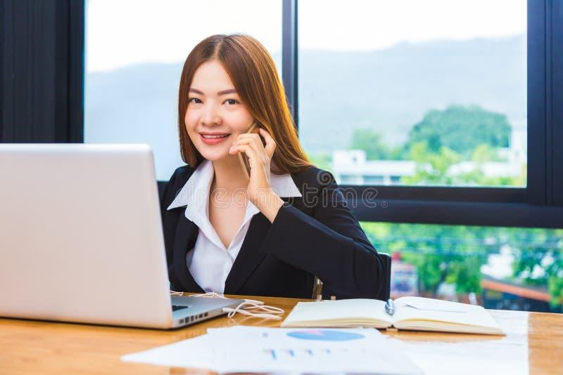 Giovane donna di affari asiatica felice attraente che usando il suoi telefono e w fotografia stock libera da diritti