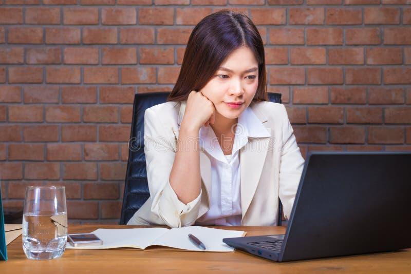 Giovane donna di affari asiatica nel vestito di colore del ligth che lavora tardi su He fotografia stock libera da diritti
