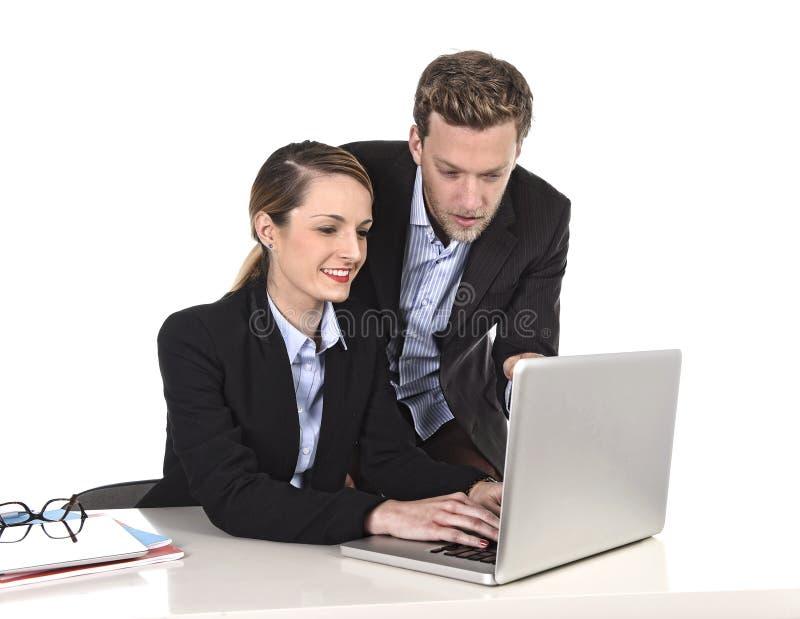 Giovane donna di affari attraente che lavora al computer portatile del computer in ufficio che parla con sorridere del collega de immagine stock libera da diritti