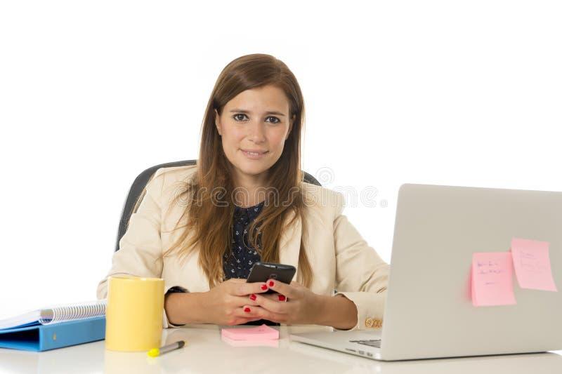 Giovane donna di affari attraente del ritratto corporativo alla sedia dell'ufficio che lavora allo scrittorio del computer portat fotografia stock