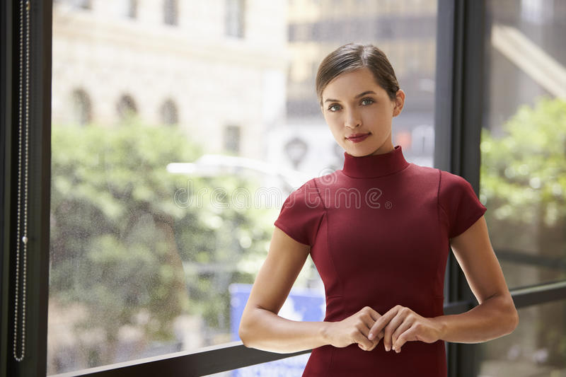 Giovane donna di affari bianca che pende da una finestra sul lavoro fotografia stock libera da diritti
