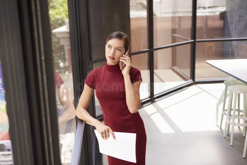 Giovane donna di affari bianca sul telefono che guarda fuori la finestra dell'ufficio fotografie stock