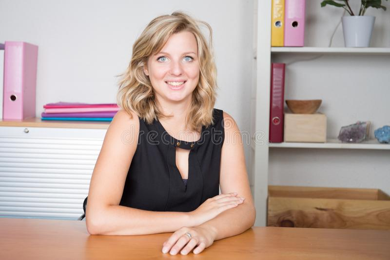 giovane donna di affari bionda attraente con il sorriso adorabile nell'ufficio fotografie stock