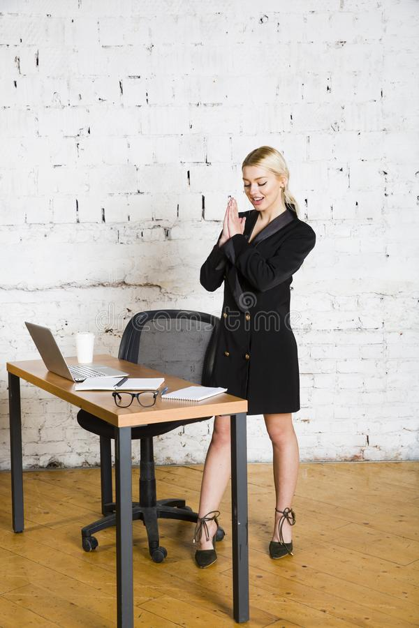 Giovane donna di affari bionda di bellezza che si siede ad una tavola dell'ufficio con il computer portatile, il taccuino ed i ve fotografia stock