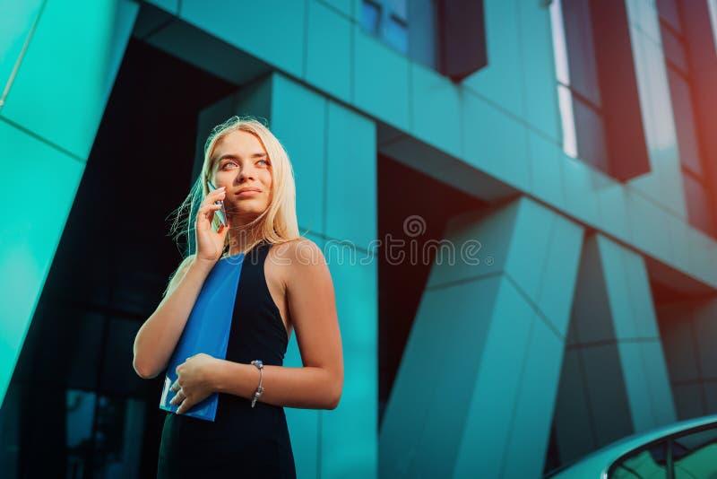 Giovane donna di affari bionda che rivolge allo smartphone e che tiene cartella dal centro di affari in città Communiation immagine stock
