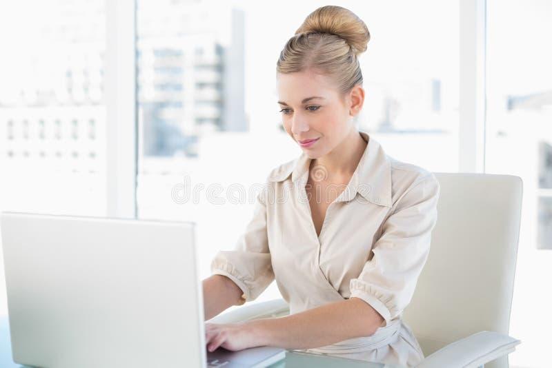 Giovane donna di affari bionda concentrata che per mezzo di un computer portatile immagini stock