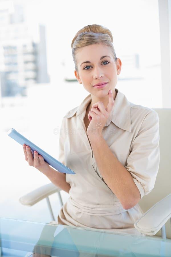 Giovane donna di affari bionda pensierosa che tiene un pc della compressa immagine stock