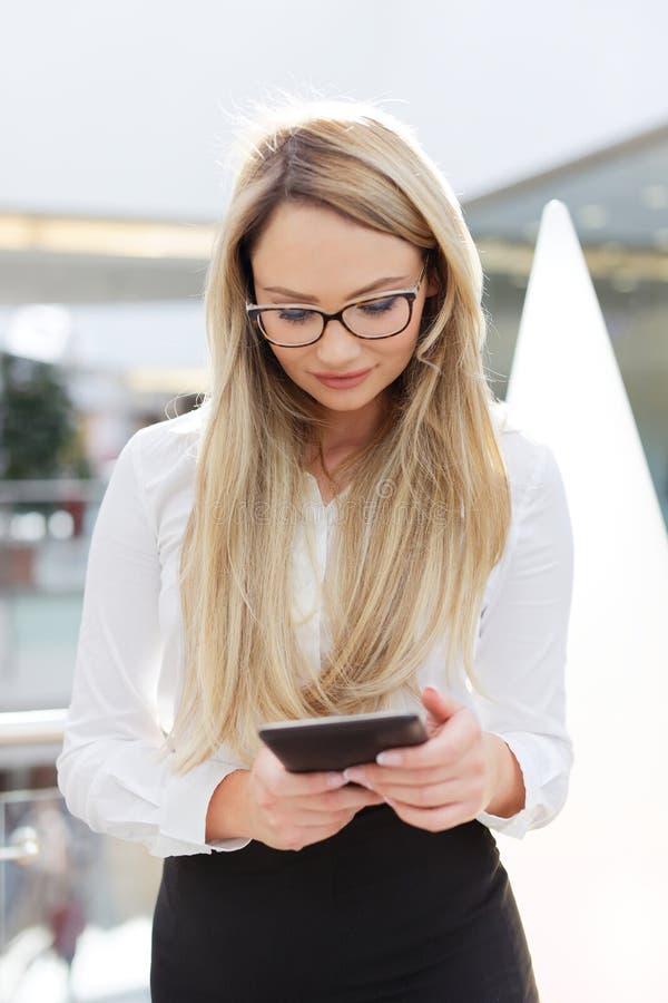 Giovane donna di affari bionda in vetri facendo uso della compressa digitale all'interno fotografia stock libera da diritti