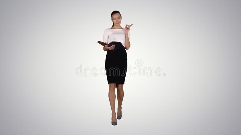 Giovane donna di affari che cammina e che legge dal taccuino sul fondo di pendenza fotografie stock libere da diritti