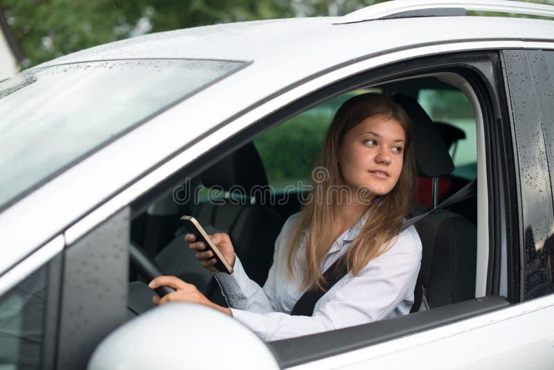 Giovane donna di affari che conduce automobile e che parla sul telefono cellulare immagini stock libere da diritti