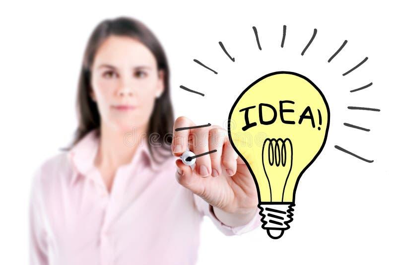 Giovane donna di affari che disegna una lampadina. fotografia stock libera da diritti