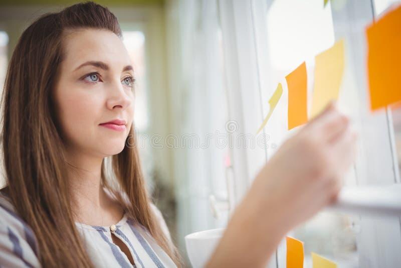 Giovane donna di affari che esamina le note adesive sulla finestra in ufficio creativo fotografia stock