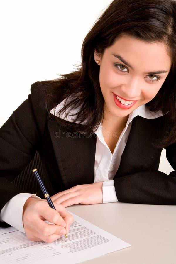 Giovane donna di affari che firma un documento fotografia stock libera da diritti