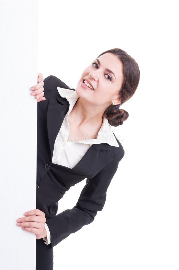 Giovane donna di affari che guarda da dietro la parete bianca immagini stock libere da diritti