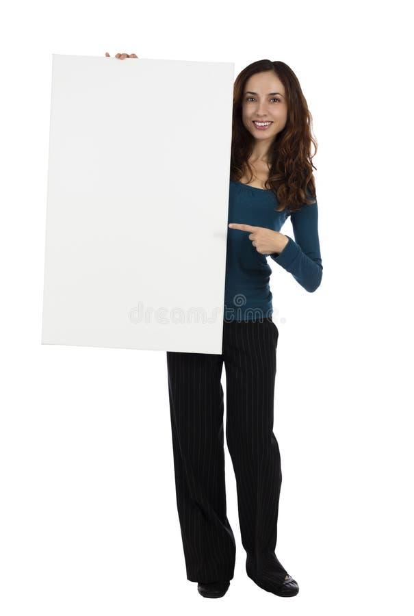 Giovane donna di affari che indica un cartello in bianco immagini stock libere da diritti