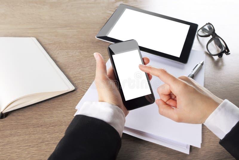 Giovane donna di affari che lavora con il telefono astuto e la compressa digitale immagini stock libere da diritti