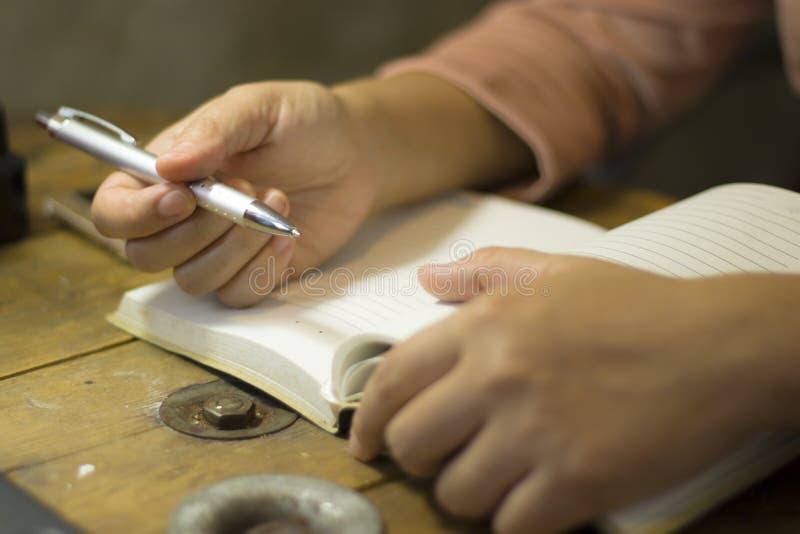 Giovane donna di affari che lavora con una penna all'ufficio, lei che resta fuori orario fotografia stock
